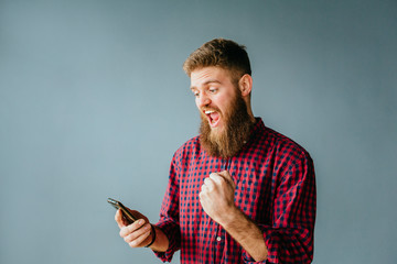 Emotional portrait of beard hipster man screaming while looking on his mobile phone over gray background. Unleashing his emotions.