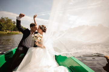 Happy and smiling bride with bridegroom in the boat
