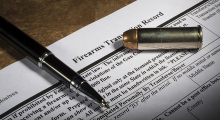 FBI gun background check form with pen and bullet