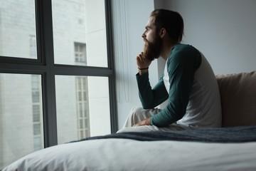 Man looking through window in bedroom
