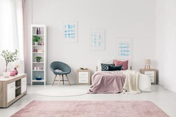 Posters in pastel bedroom interior
