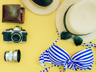 flat lay for blue bikini girl summer cloth and accessories concept with yellow background , camera and wallet