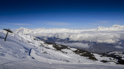 Chairlift at Italian ski area of Pila on snow covered Alps and pine trees during the winter with Mt. Blanc in France visible in background