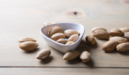 Almonds in white shell on wooden table