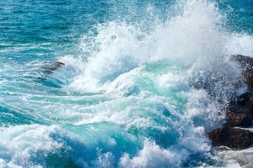Beautiful blue wave in tropical ocean. Turquoise wave barrel crashing on rocks. Close up.