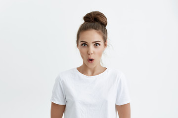 Portrait of attractive modern european model expressing surprise and excitement while glancing at camera with desire and standing with opened mouth over white background. Woman is shocked of huge sale