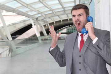 Furious businessman screaming on public phone