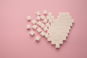 Broken heart made of sugar cubes. Rupture of relations. Sugar kills. Pink background.
