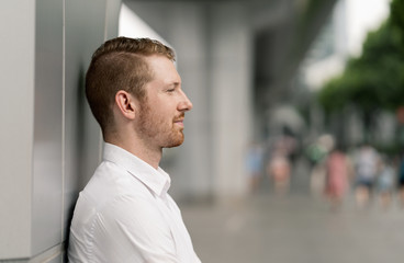 Young businessman leaning against wall in city, Shanghai, China