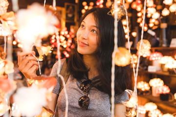 Tourist admiring decorative lights in bazaar, Bangkok, Thailand