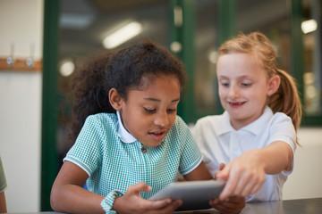 Two schoolgirls looking at digital tablet in classroom at primary school