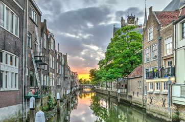 A canal in the old medieval town centre of Dordrecht, the Netherlands, with houses on both sides and an orange red sunset in the distance