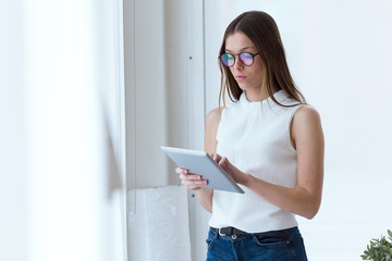 Business young woman using her digital tablet in the office.