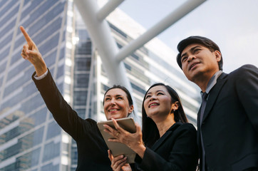 group of business people in suit pointing up and looking up to future with mobile tablet standing together in modern city, successful, support, meeting, partner, teamwork, network technology concept