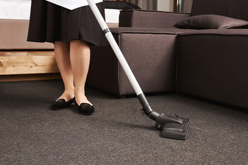 Dirt have no chances to survive. Cropped portrait of woman in maid uniform cleaning floor with vacuum cleaner, working in house of her employer, wiping all dirt and mess they left after party