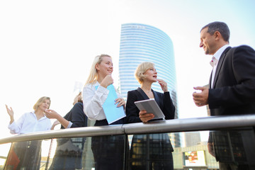 Business colleagues discussing crypto currency in La Defense Paris. Concept of talking about financial decisions with boss. Young employees speaking and wearing white shirts.