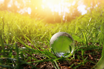 low angle small crystal globe in the grass. travel and global issues concept.