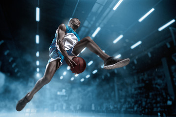 Basketball player on big professional arena during the game. Basketball player making slam dunk.