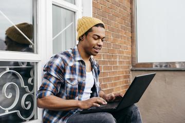 Ethnic man using laptop on balcony