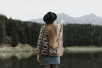 Back view of fashionable young woman wearing hat and poncho standing in front of a lake