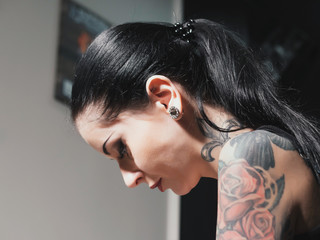 Young beautiful womans face, she makes tattoo. Close up working with machine.