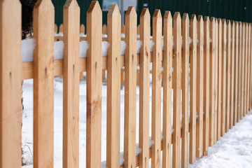 Wooden fence covered with snow around garden in winter time.