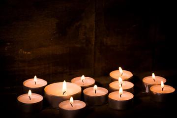 tealight candles on dark wooden background