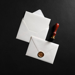 Vintage envelope with golden wax seal, stamp and postcard on black paper background. Flat lay.