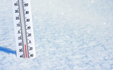 Winter background with thermometer in clean shiny snow.