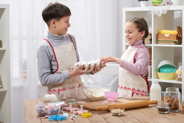 Child girl and boy cooking in home kitchen, hold eggs in the hands