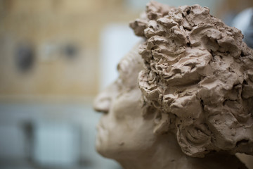 Close up of a raw clay bust sculpture in an art studio with copy space