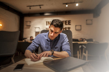 Handsome young businessman working with laptop inside on a wooden table. Light filter effect