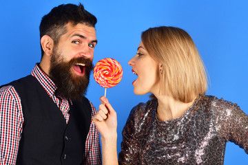 Woman and bearded man eat lollipop on blue background