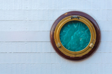 Ship golden portholes on white wooden background. Ship window or porthole on white wooden wall.