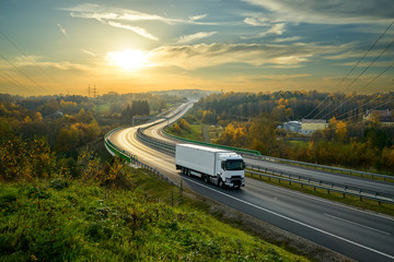 Fotobehang - White truck driving on the highway winding through forested landscape in autumn colors at sunset