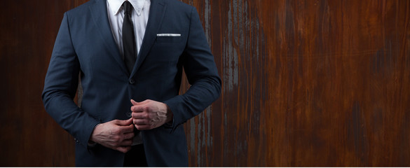 body of a businessman in a suit on rusty background