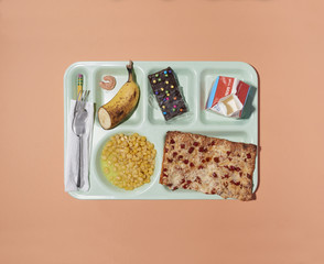 Overhead view of school lunch tray isolated on peach background