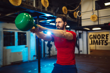 Handsome man doing a weight training by lifting kettlebell.