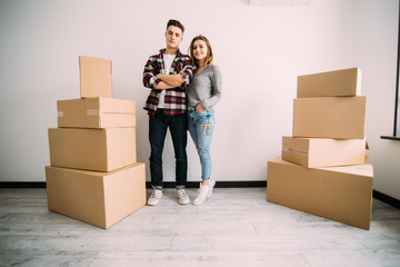 Happy couple standing near boxes in their new apartment. Relocation and moving.