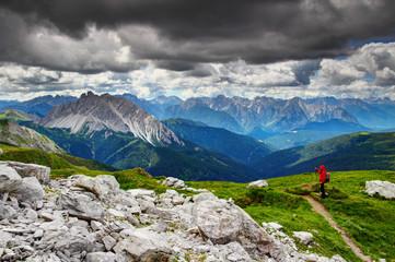 Hiker takes photos of extremely sharp Crode dei Longerin peak Alpi Carniche Belluno Veneto from Karnischer Hohenweg Traversata Carnica long distance trail