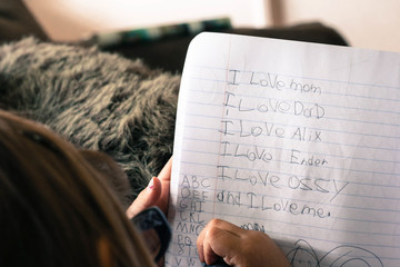 Close up on Little girls hand writing in a notebook