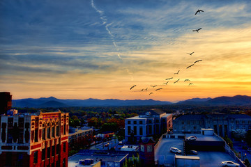 Asheville North Carolina at sunset with the Blue Ridge Mountains in the distance.