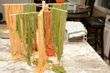 Colorful red and green fresh made pasta drying on wooden tree rack