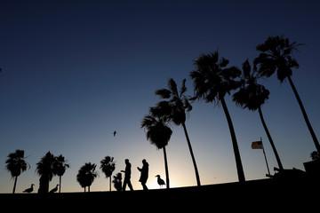 People are seen in silhouette walking on Venice Beach in Los Angeles