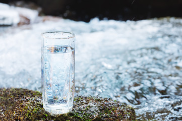 A transparent glass glass with drinking mountain water stands in the moss stone on sun beame against a background of a clean frost mountain river. The concept of drinking mountain drinking mineral