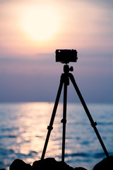 silhouette vintage camera on tripod shooting beautiful calm sea with sun reflection on water at sunset