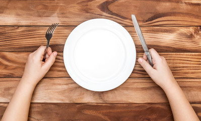 Hungry child waiting for meal. Child's hands holding fork and knife over table with empty dish. Top view.