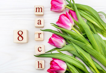 Wooden cubes with date of 8 march and tulips on the wooden background. Holiday background. Top view.