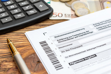 German tax form with pen,money and calculator on the table. Close up.