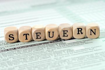 Steuern / Formular und Holzwürfel mit dem Wort Steuern